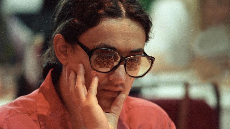 La femme est assise devant un jeu d'échecs et se tient le visage avec une main.