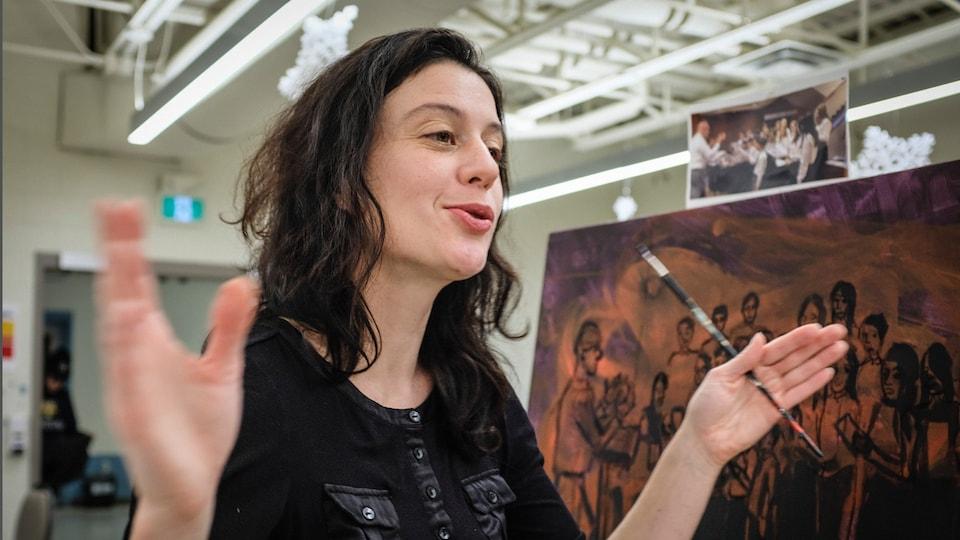 Norah Pendergast devant une toile de peinture.