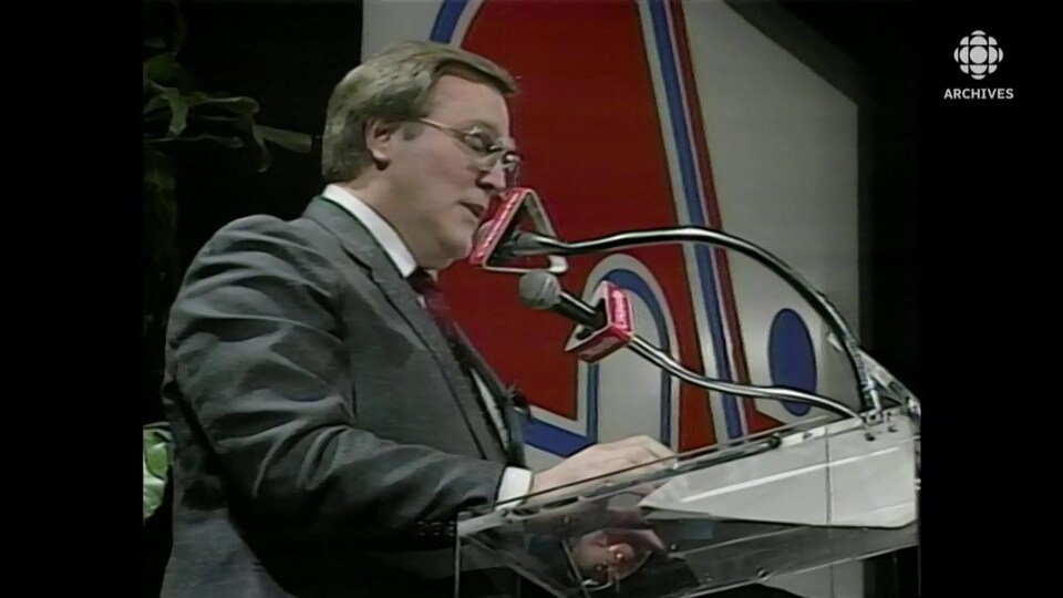 Marcel Aubut, en conférence de presse. Le logo des Nordiques trône en arrière-plan.