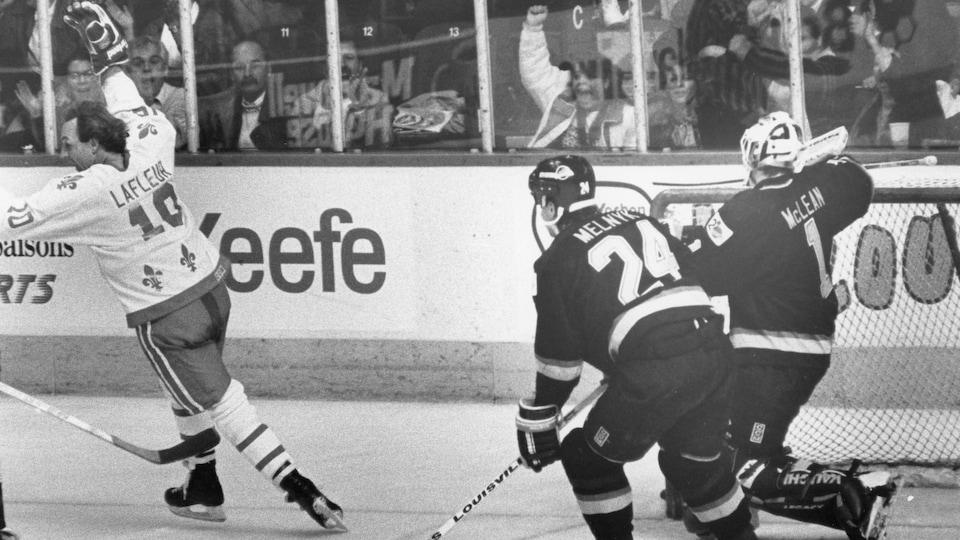 Guy Lafleur vient de marquer pour les Nordiques lors d'un match contre les Canucks de Vancouver au Colisée, en novembre 1989. Il file en levant le bras en l'air en signe de victoire, alors que les Canucks derrière peinent à suivre le rythme.