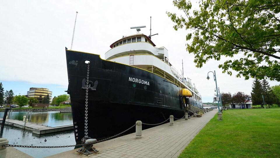 Un navire noir amarré à un quai