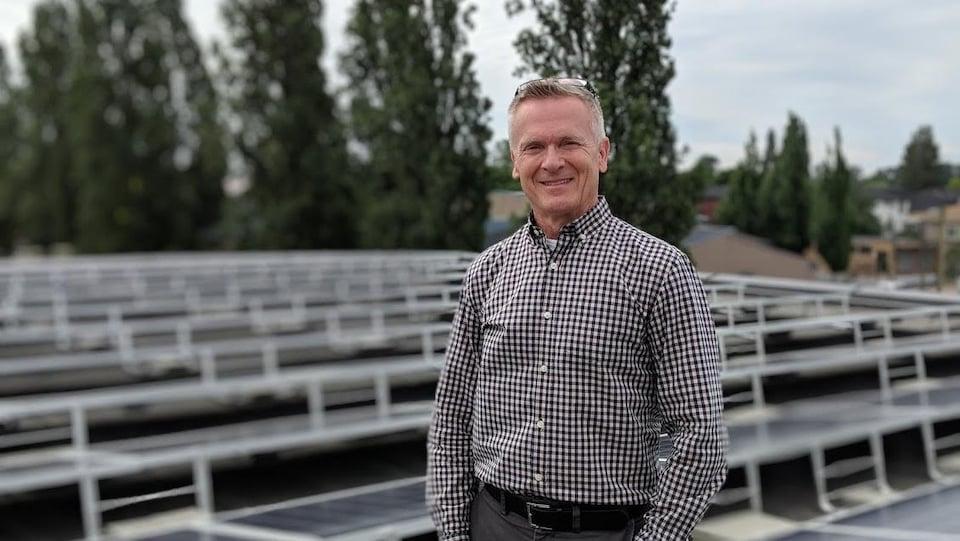 Un homme debout devant des panneaux solaires.
