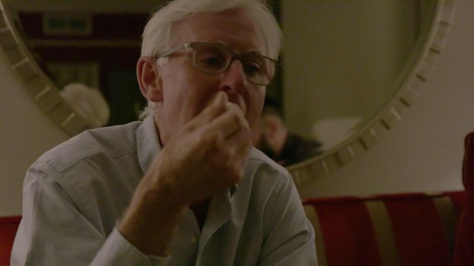 Un homme portant des lunettes goûtant à quelques gouttes d'huile de cannabis en plaçant un applicateur sous la langue.