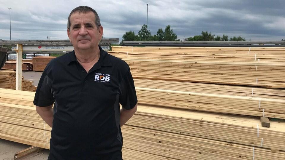 Un homme devant des morceaux de bois.
