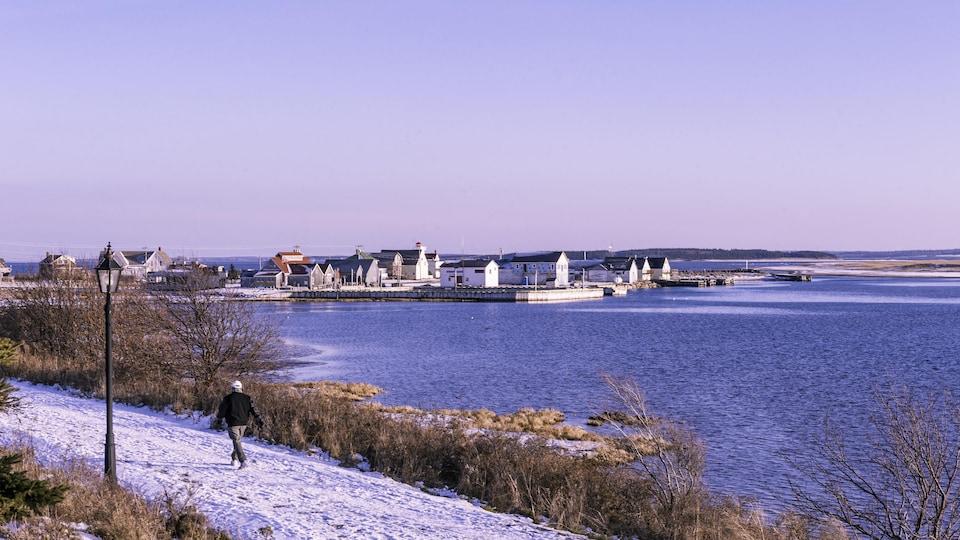 Un homme marche sur un sentier partiellement enneigé en décembre à l'Île-du-Prince-Édouard.