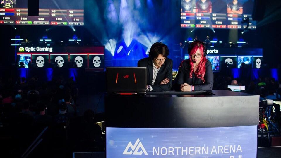 un animateur et une animatrice parlent sur une scène au Centre Bell lors d'un événement de sport électronique.
