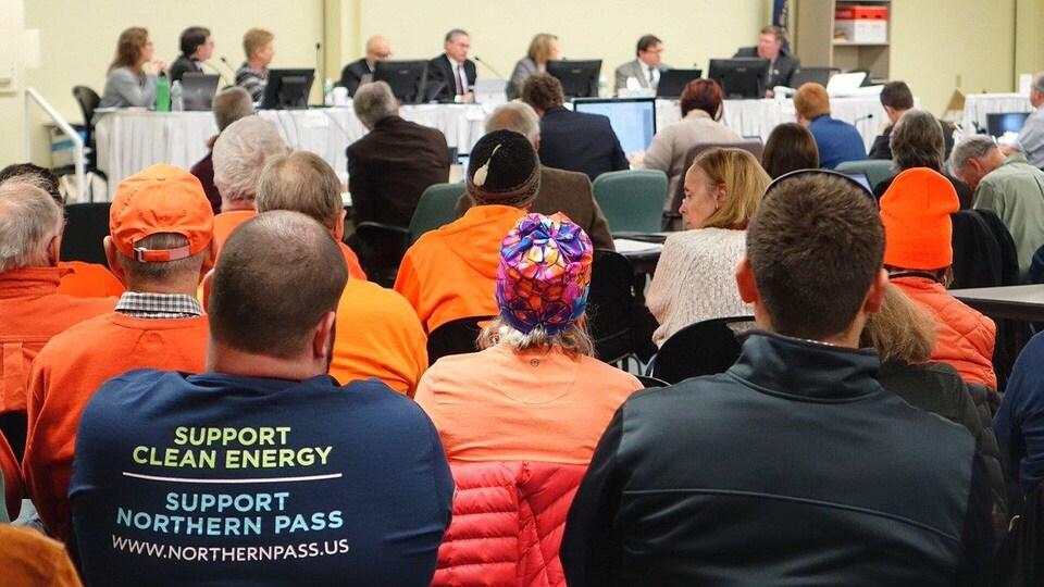 Des gens, vus de dos, écoutent les délibérations. À l'avant-plan, un homme porte un chandail sur lequel on peut lire : «Soutenez l'énergie propre. Soutenez Northern Pass».