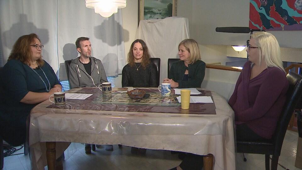 De gauche à droite : Sarah Hoffman, Philip et Michelle Baer, Rachel Notley et Colleen Wasson. Ils sont tous assis autour d'une table.