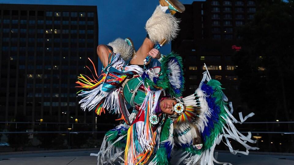 Notorious Cree, en habit traditionnel, fait une posture dans la rue de nuit.