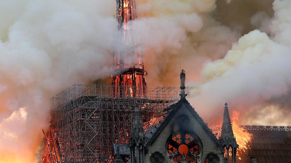 La flèche et des échafauds sur le toit de la cathédrale Notre-Dame de Paris sont en feu entourés de colonnes de fumée.