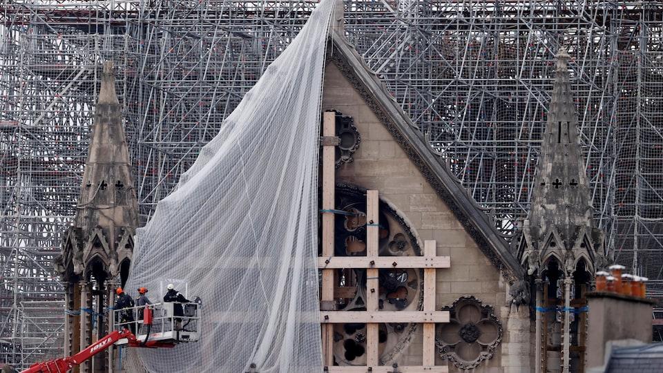 Des hommes retirent une toile sur un pignon de la cathédrale.