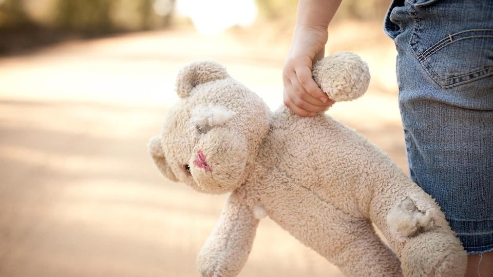 Une vieille peluche dans la main d'un enfant qui marche.