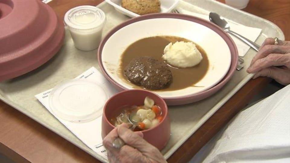 Un plat de nourriture servi à une personne âgée