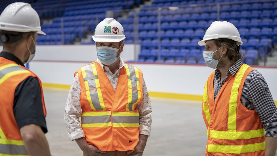 Le maire de Trois-Rivières, Jean Lamarche, est vêtu d'une chemise de sécurité et d'un casque protecteur. Il discute avec deux personnes.