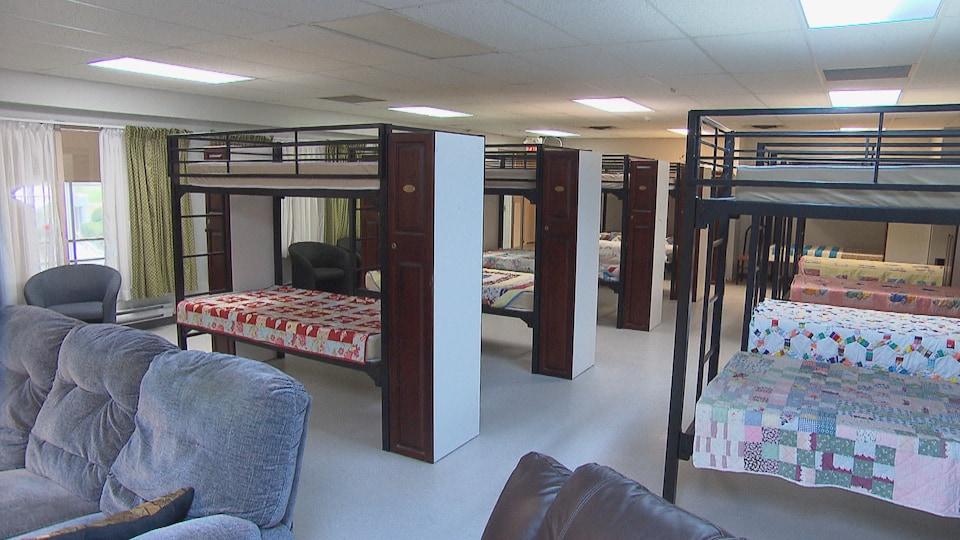 Un dortoir avec  des lits superposés et des canapés à l'avant-plan.