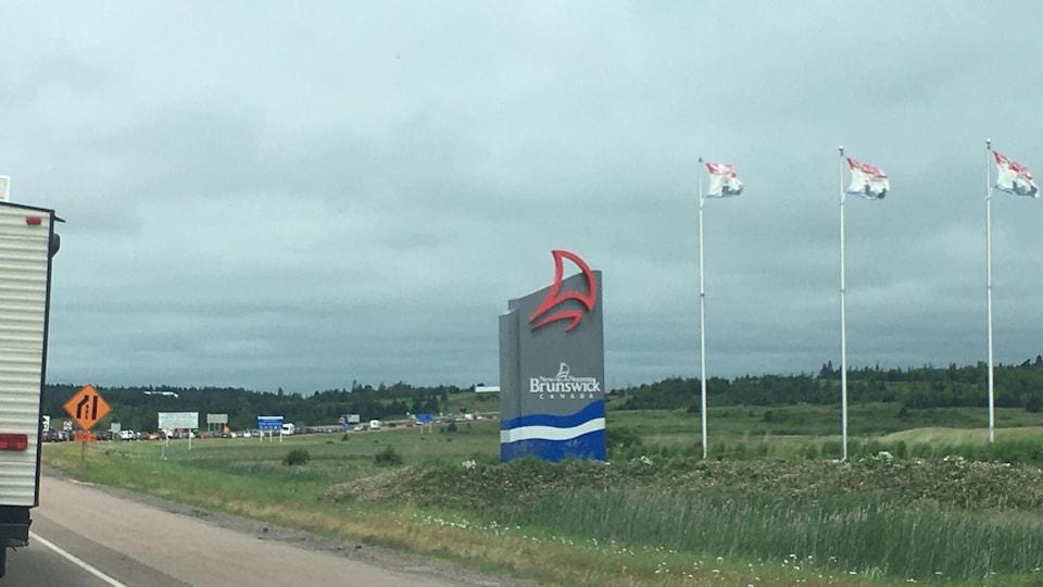 Autoroute d'entrée du Nouveau-Brunswick avec trois drapeaux.