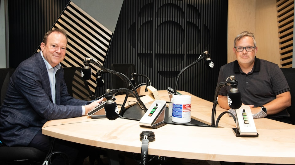Deux hommes assis derrière un micro sourient à la caméra