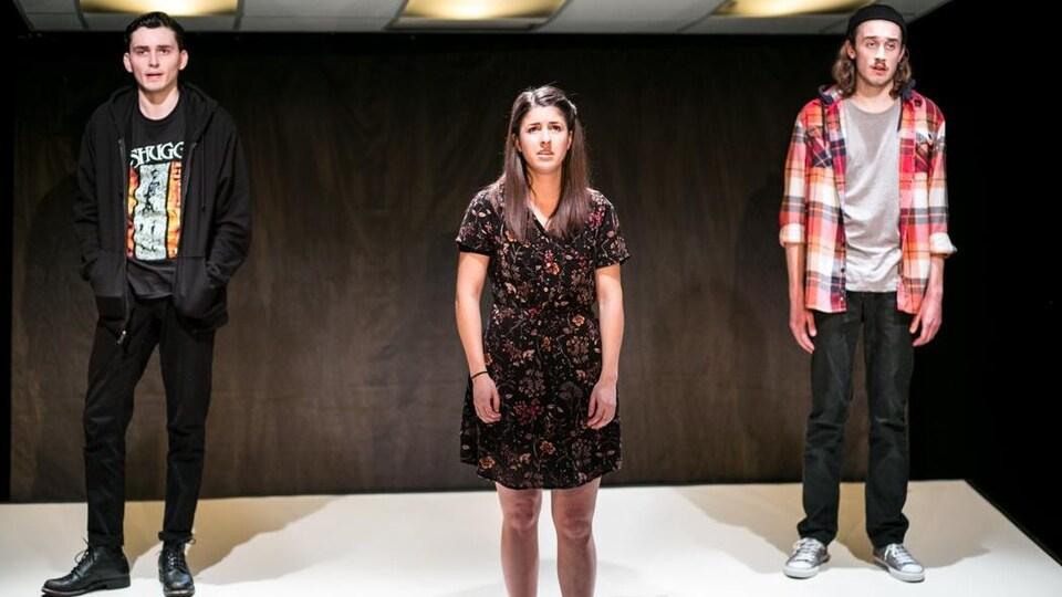 Trois comédiens, l'air découragé, sur scène.