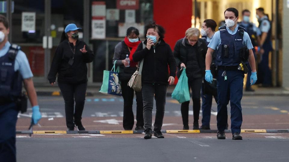 Des gens sont escortés par la police à la sortie d'un supermarché d'Auckland, en Nouvelle-Zélande.
