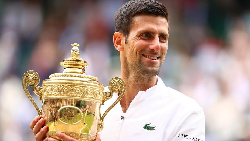 Il tient le trophée.