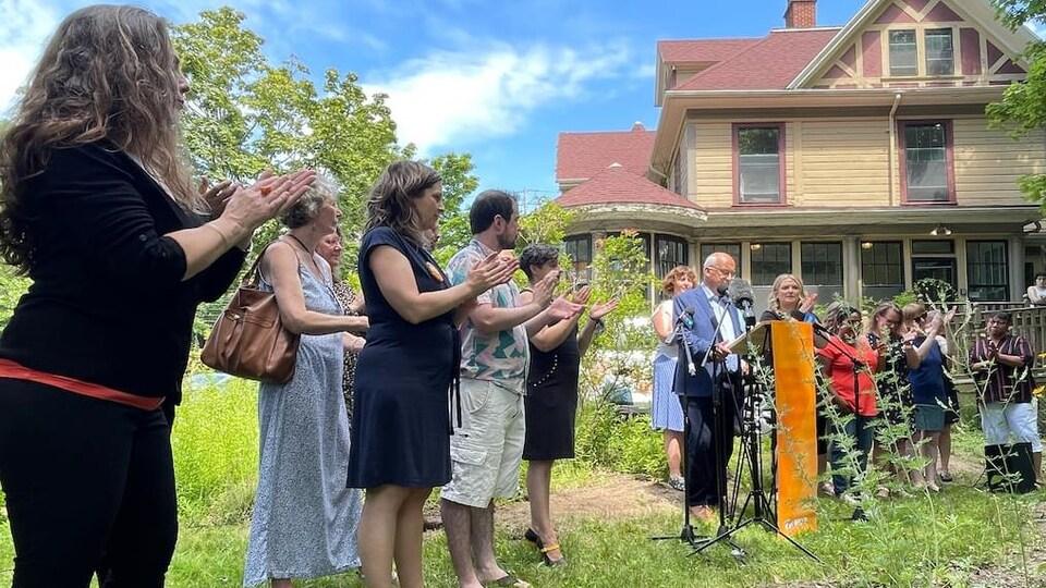 Le chef se tient debout derrière un lutrin dans un jardin, en compagnie des candidats du parti.