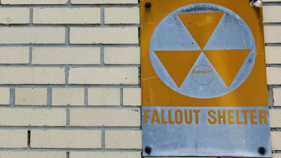 Un panneau de métal jaune indiquant la présence d'un abri contre les retombées radioactives est posé sur un mur de briques.