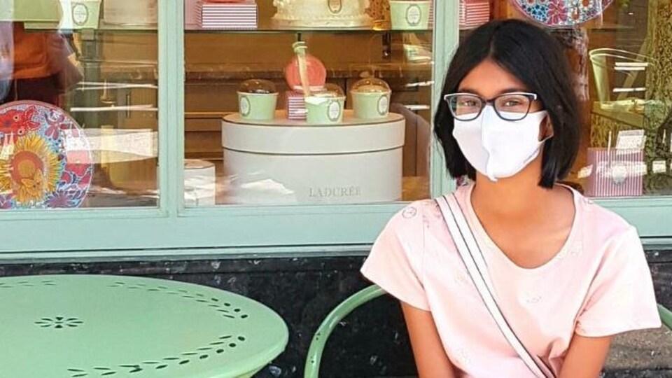 Nuha Patel est assise à une table, devant une boutique.