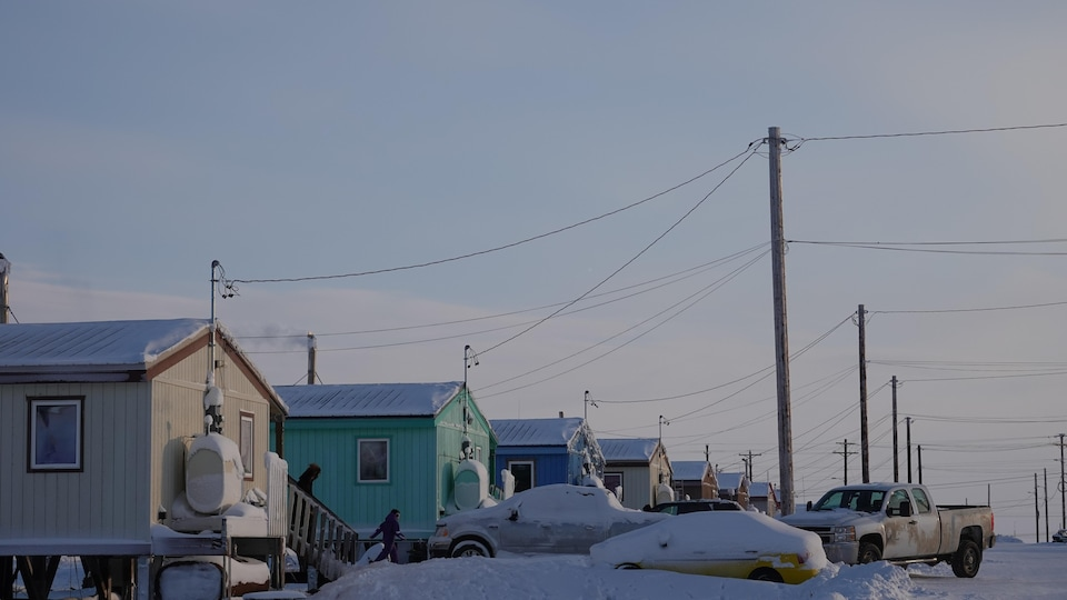 Des maisons colorées et des voitures sont recouvertes de neige à Nuiqsut.