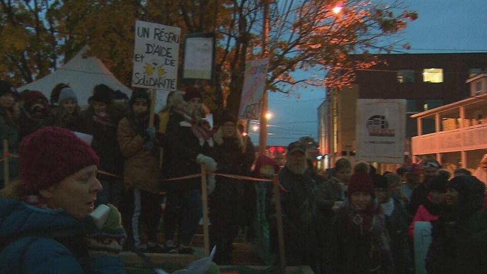 """Une dame porte une pancarte indiquant """"un réseau d'aide et de solidarité""""."""