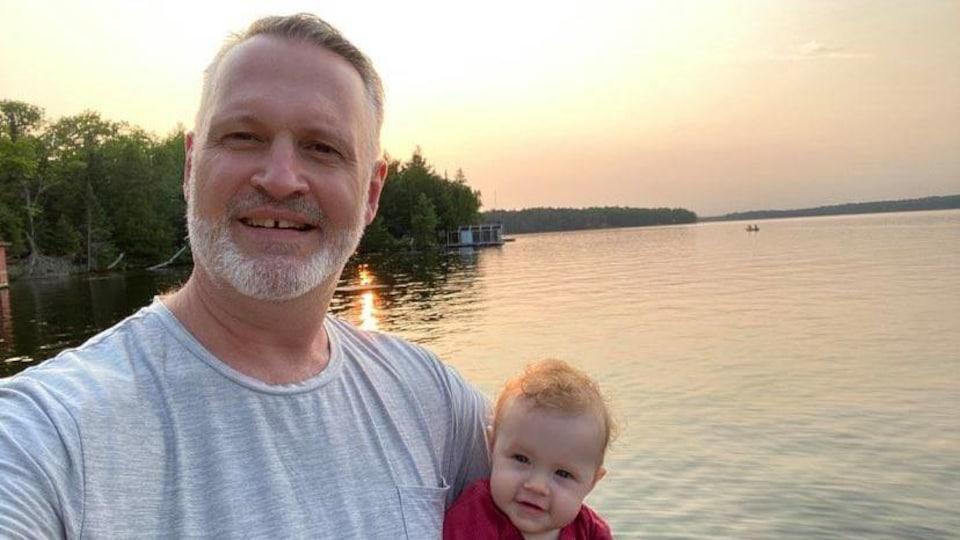 Égoportrait de Tim Brown devant un lac, sa fillette dans les bras.