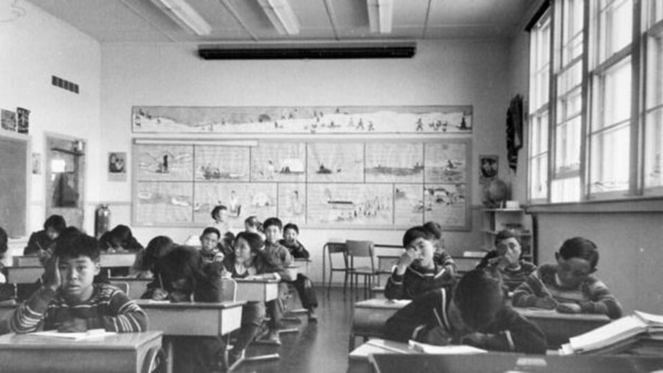 Des élèves de l'externat fédéral Sir Joseph Bernier de Chesterfield Inlet sont assis derrière leur pupitre, le 5 septembre 1958.