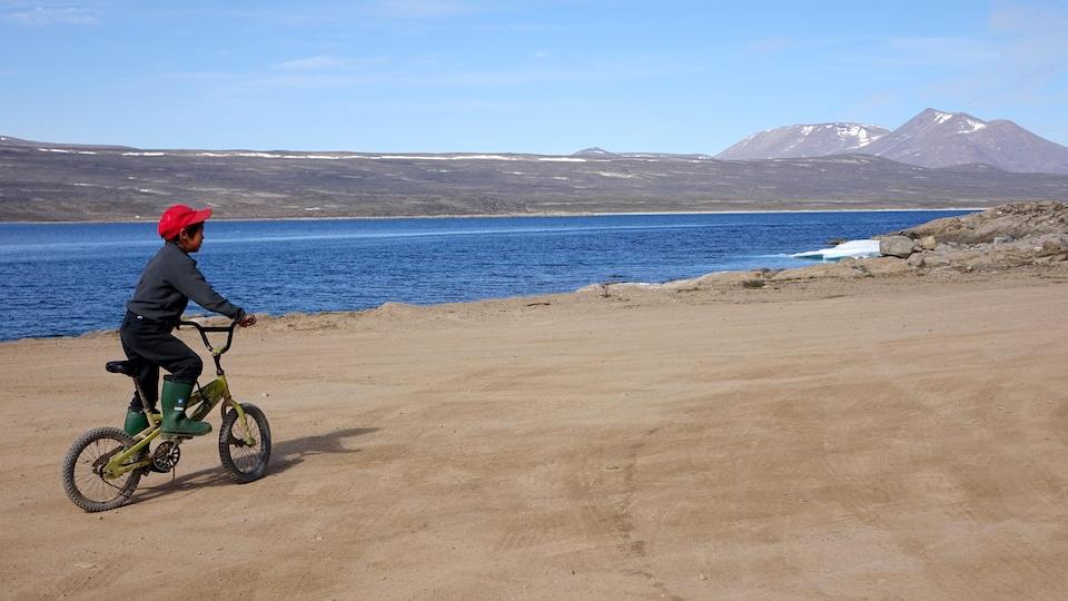Un enfant fait de la bicyclette dans une rue de Clyde River, au Nunavut.