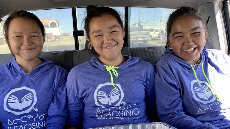 Trois jeunes filles sont assises sur la banquette arrière d'une voiture.