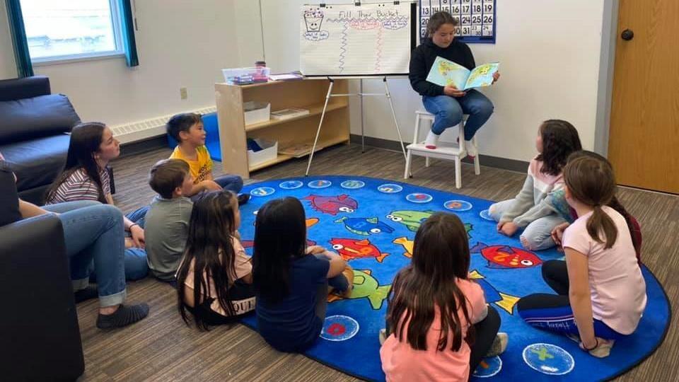Des enfants sont assis en cercle sur le sol.