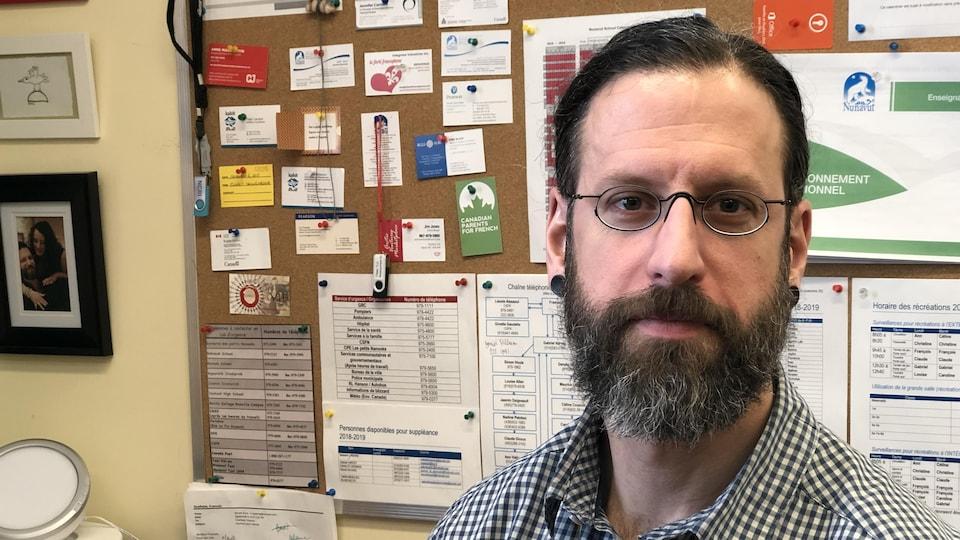 Un homme qui porte des lunettes et une barbe sourit à la caméra.