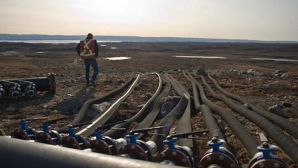 Un travailleur marche le long de tuyaux étendus sur le sol.