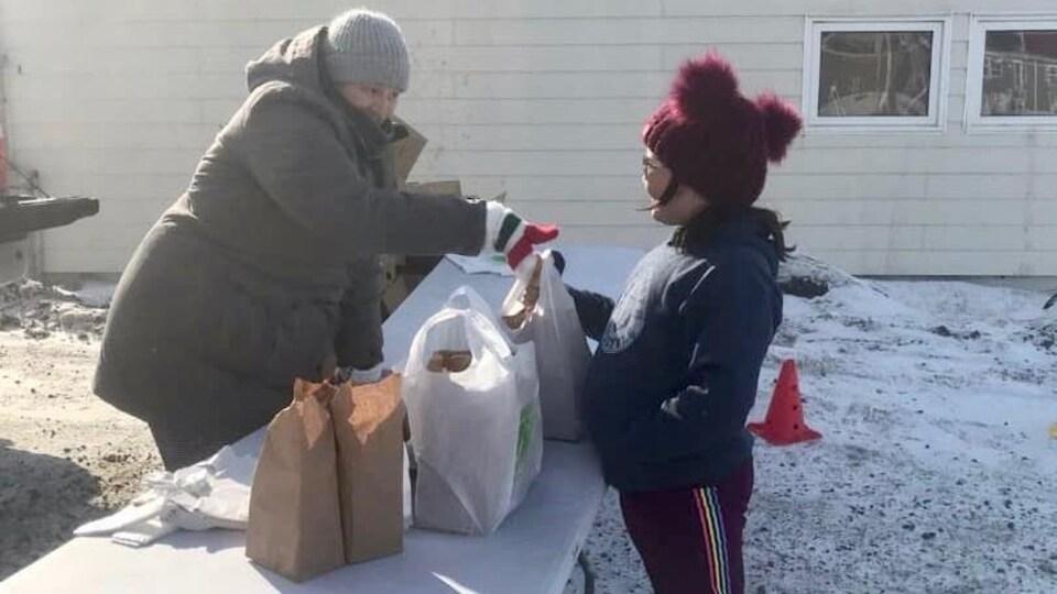 Une femme offre un petit déjeuner à une enfant.