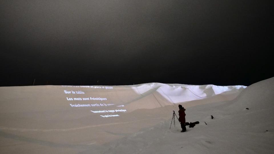 Un poème est projeté sur de la neige dans la toundra.
