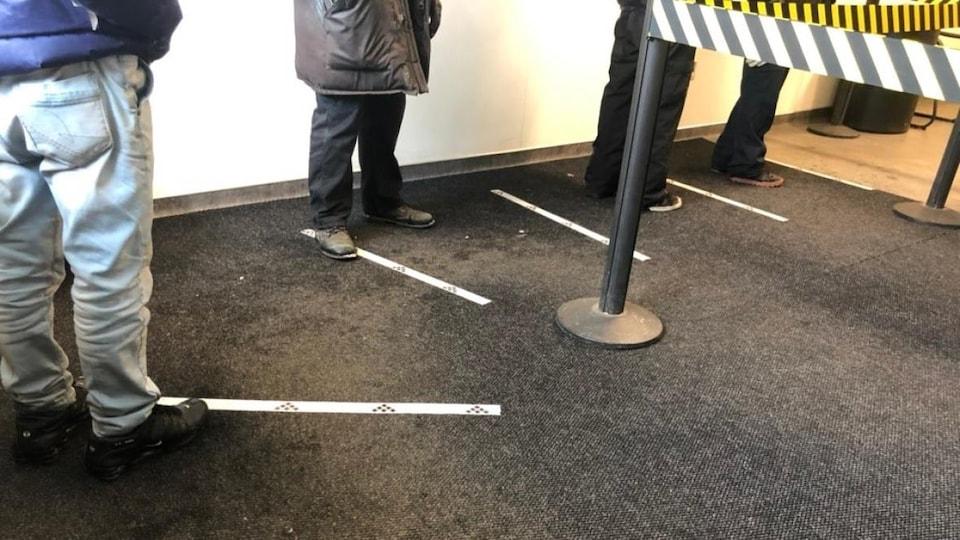 Des rubans adhésifs sont collés sur le plancher d'un magasin pour rappeler aux clients de garder leurs distances les uns entre les autres.