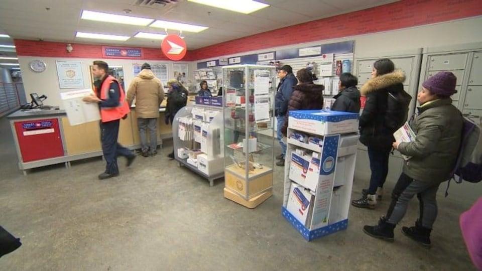 Des clients attendent en file dans un bureau de poste.