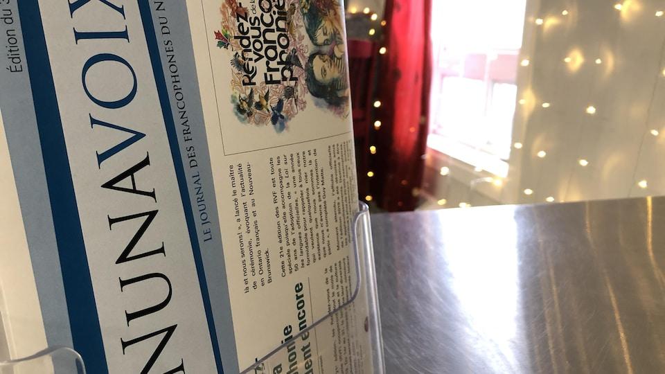 Présentoir de journaux sur un comptoir avec des lumières décoratives à l'arrière.