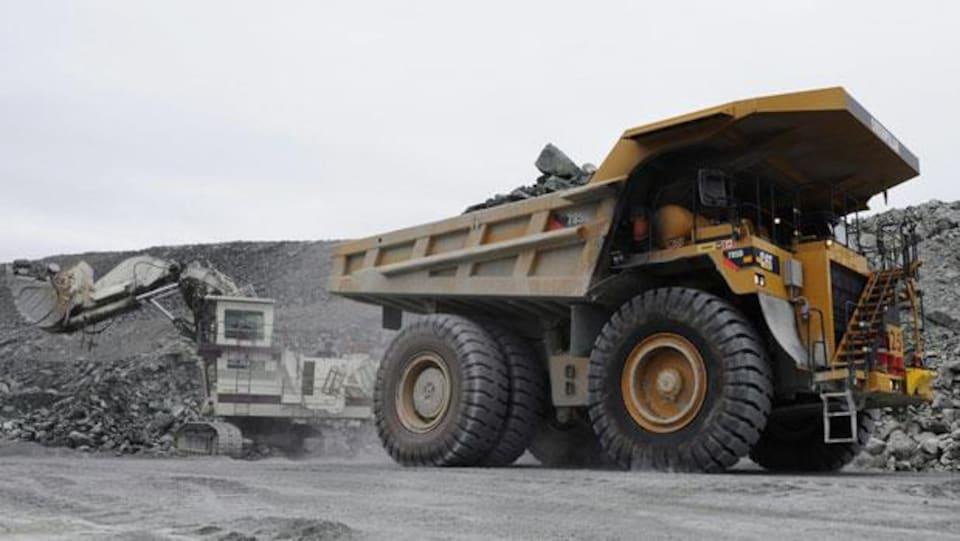 Un camion lourd transporte de la roche dans une carrière.