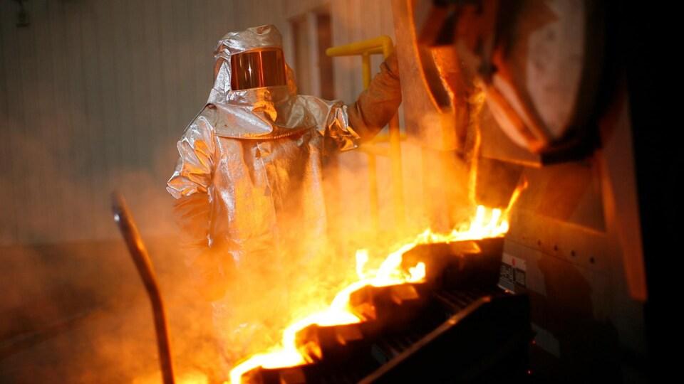 Un travailleur en habit protecteur regarde une coulée de métal.