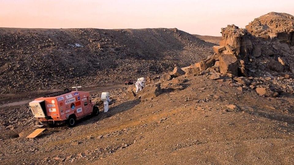 Deux chercheurs habillés de combinaisons spatiales prélèvent des échantillons dans le cratère.