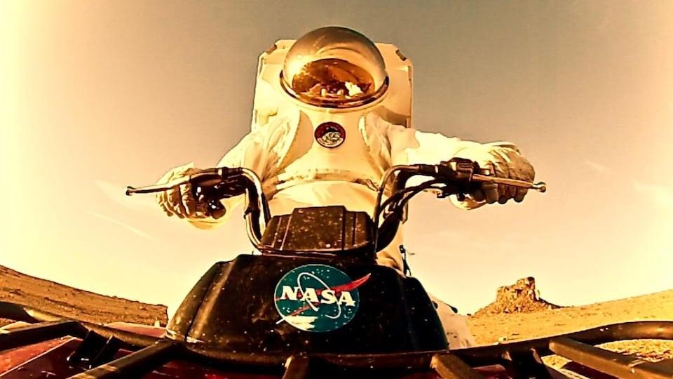 Un scientifique vêtu d'une combinaison spatiale conduit un quatre-roues sur l'île Devon, au Nunavut.