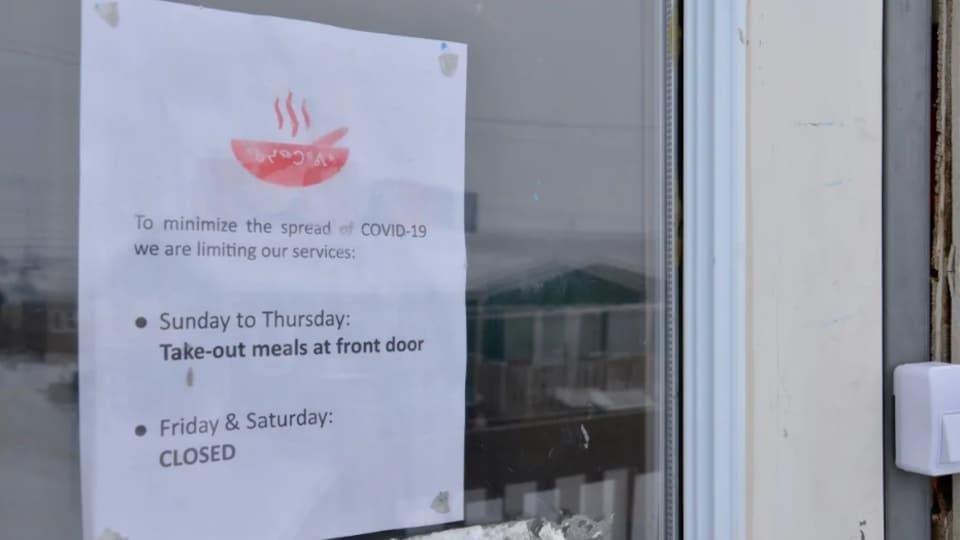 Une affiche apposée sur la porte d'entrée du centre alimentaire de Qajuqturvik au Nunavut informe les clients du nouvel horaire  de services.
