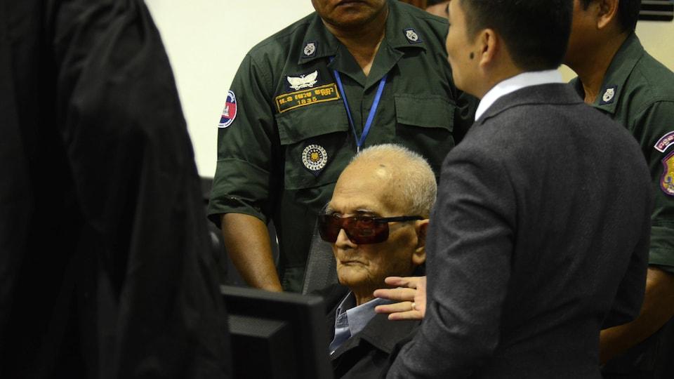 Un vieil homme, qui porte des lunettes, est assis dans une salle de cour en attendant le verdict dans le procès qu'il subit.