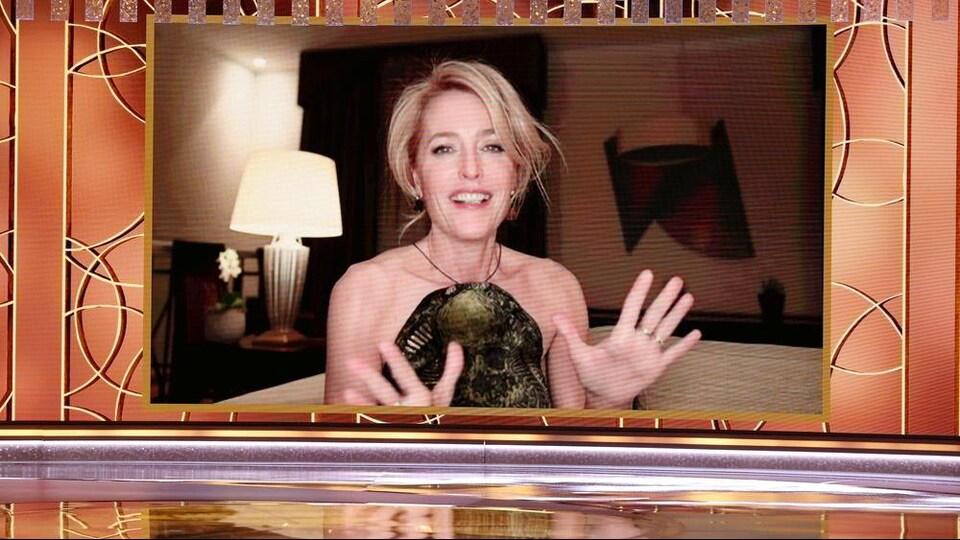 L'actrice Gillian Anderson dans un écran sur une scène.