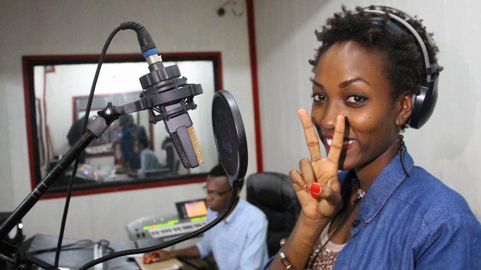 L'autrice-compositrice-interprète Nyenimana dans un studio d'enregistrement au Burundi. L'ingénieur de son est assis devant sa console.