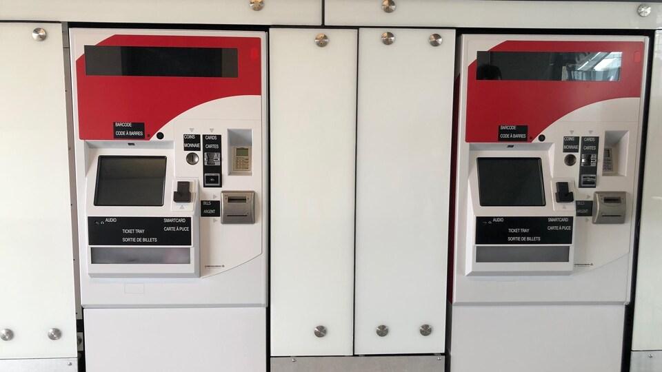 Deux distributrices de billets rouge et blanche.